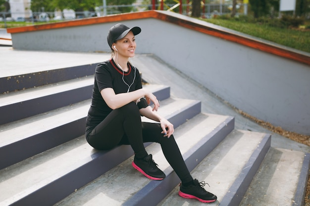 Young athletic smiling woman in black uniform and cap with headphones listening to music, resting and sitting before or after running, training on stairs in city park outdoors