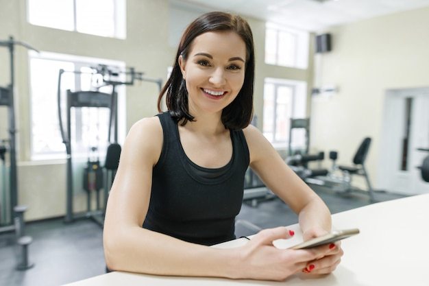 Young athletic smiling woman in the gym with mobile phone