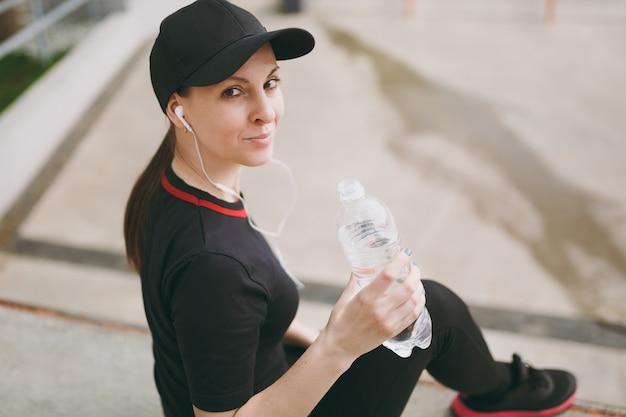 黒い制服を着た若い運動笑顔の女性、ランニングの前後に座っている水でボトルを保持している音楽を聴いているヘッドフォンでキャップ、屋外の都市公園でトレーニング