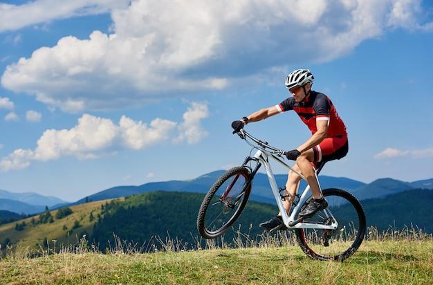 Молодой спортивный спортсмен турист байкер в профессиональной спортивной одежде, поворачиваясь на одном колесе велосипеда