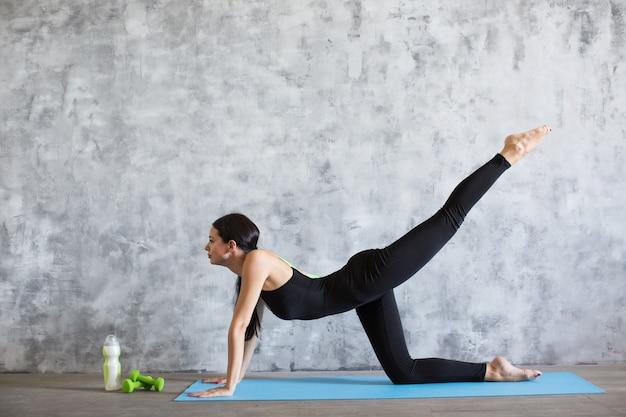 Молодая атлетичная спортивная стройная женщина делает упражнения йоги в тренажерном зале. растяжка в помещении.