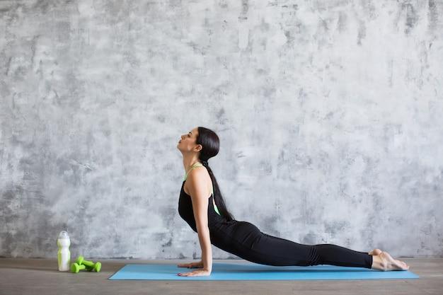 Молодая атлетичная спортивная стройная женщина делает упражнения йоги в тренажерном зале.