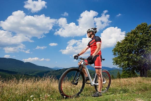 Молодой атлетический туристический велосипедист стоя с велосипедом на травянистой долине наслаждаясь красивым видом далеких гор на яркий солнечный день. активный образ жизни и концепция экстремального спорта.