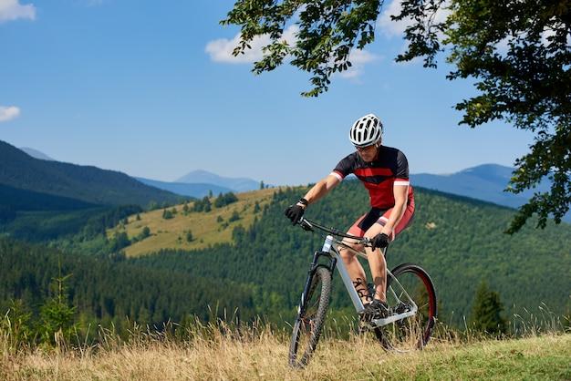 Молодой спортивный турист, езда на велосипеде в высокой траве под большой зеленой веткой на фоне красивых гор летом