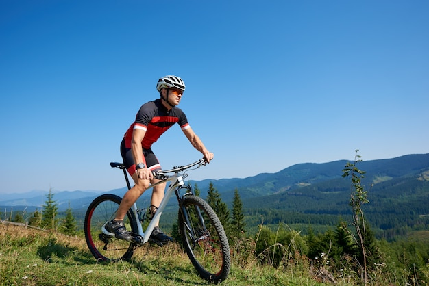 Young athletic tourist cyclist riding bike down grassy hill on distant mountains and blue summer sky background. active lifestyle and extreme sport concept.