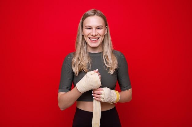若い運動女性はボクシングトレーニングの前に彼女の手を包帯します