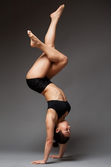 Young athletic woman in a black top and shorts performing handstand