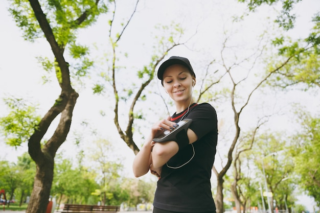 Young athletic woman in black uniform with earphones listening to music, looking on mobile phone using application, app for running or jogging, training in city park outdoors