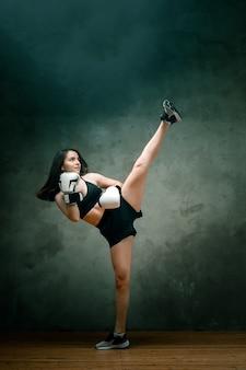 ショートパンツ、ショートトップ、ボクシンググローブを着用した若いアスリート女性ボクサーが、濃い灰色の背景で頭上でキックをしている