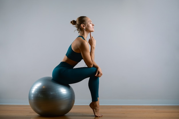 Young athletic woman doing exercises on fitball in the gym