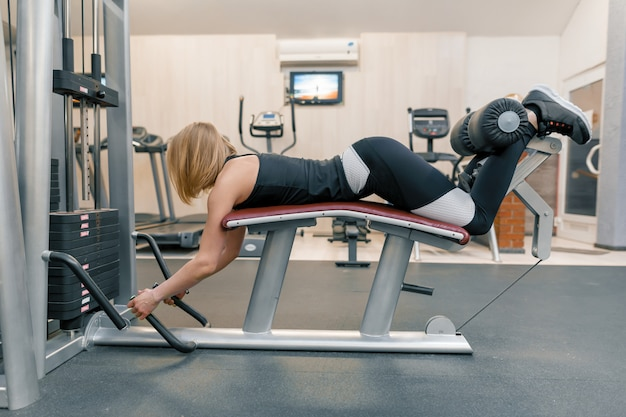 Young athletic woman doing exercises on legs and buttocks in gym