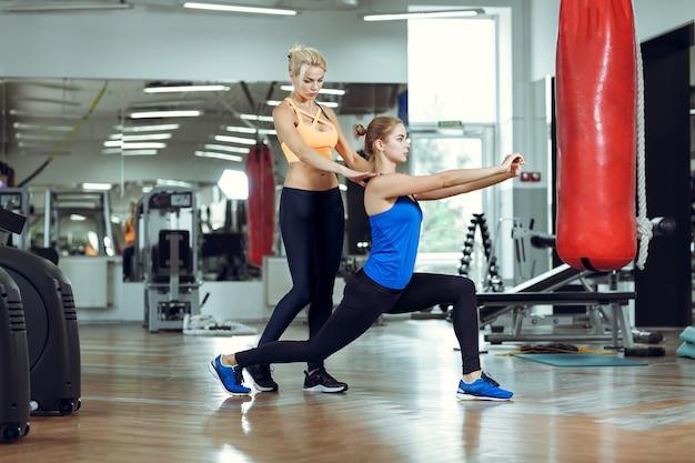 Молодая спортивная женщина делает упражнения с личным тренером по фитнесу