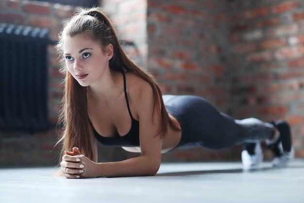Young athletic woman doing her exercise routine at home