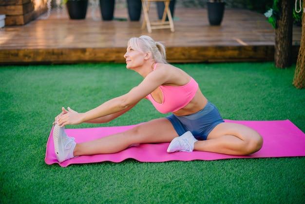 健康的なライフスタイルの緑の芝生の概念で脚の筋肉のストレッチをしている若い運動女性
