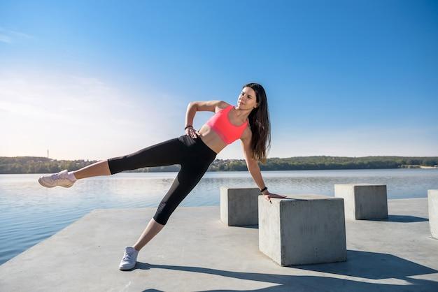 腕立て伏せをしている若い運動選手。昼間に湖の近くでフィットネス運動をしている女の子