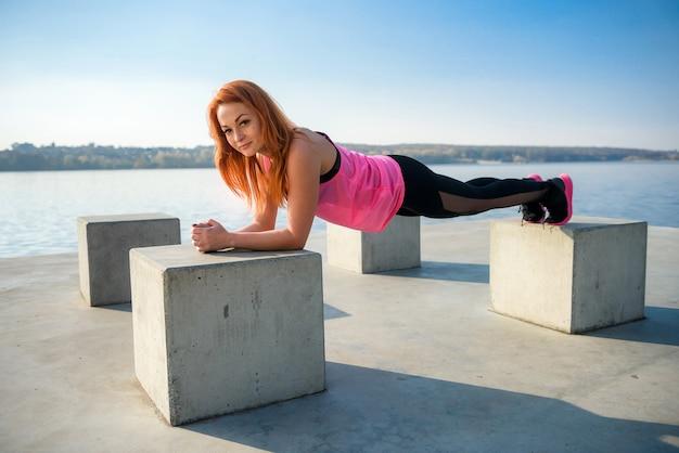 Молодая спортивная женщина делает отжимания
