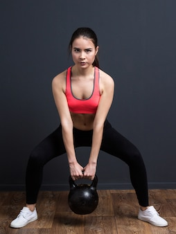 Young athletic woman doing squats with weights