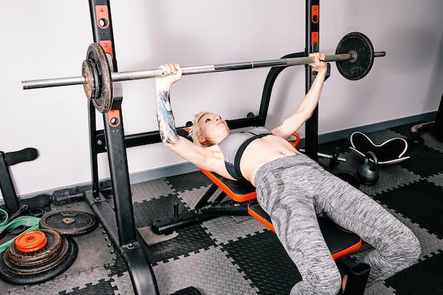 Молодая спортивная женщина делает весовую тренировку в тренажерном зале