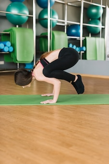 Young athletic woman doing yoga pose on green exercise mat over wooden floor