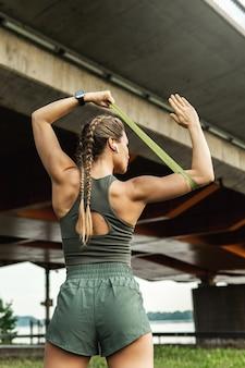 路上で抵抗輪ゴムでトレーニング中の若い運動女性