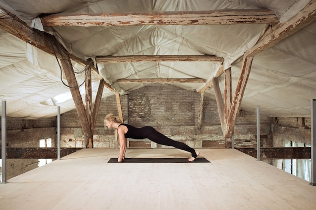 A young athletic woman exercises yoga on an abandoned construction building. mental and physical health balance. concept of healthy lifestyle, sport, activity, weight loss, concentration.