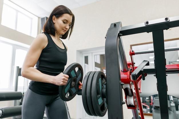 현대적인 체육관에서 기계에 운동 젊은 운동 여자