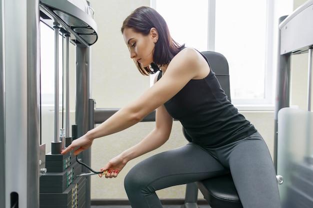 스포츠 체육관에서 기계 운동 젊은 운동 여자
