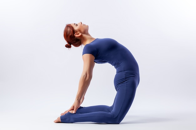 Young athletic woman gymnast in gymnastic jumpsuit does stretching in difficult poses