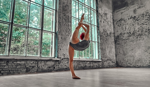 Молодая спортивная женщина в сером купальнике занимается гимнастикой. концепция йоги. девушка делает растяжку.