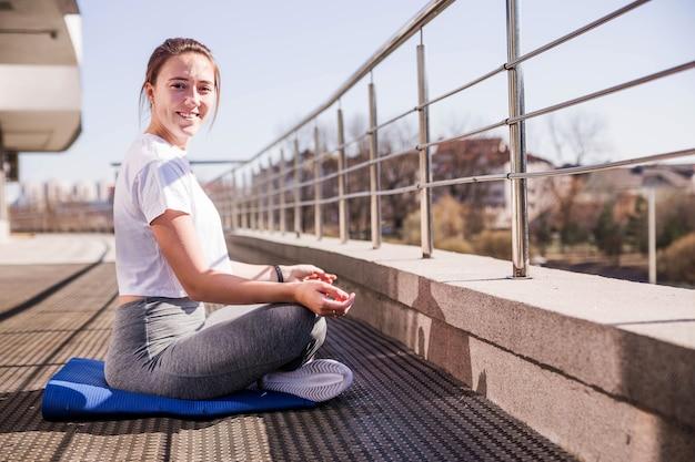 Молодая спортивная женщина в белой футболке и серых леггинсах сидит в позе лотоса на свежем воздухе в солнечную погоду на террасе. горизонтальное фото. улыбнись и посмотри в камеру