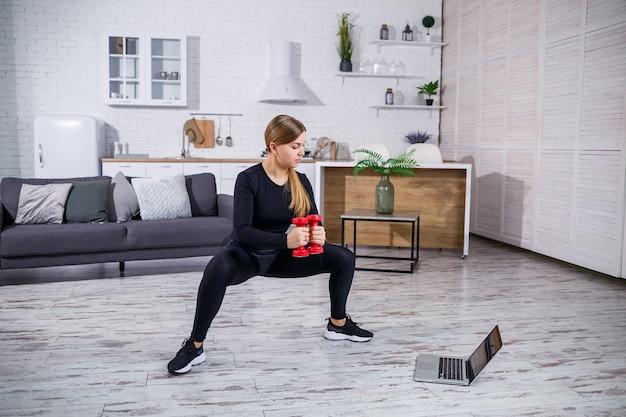 ノートパソコンのフィットネスサイトからのオンライントレーニングを使用し、自宅でスポーツをしているアパートのフィットネス服ブラックトップとレギンスの若いアスリート女性。検疫中の自宅でのフィットネス