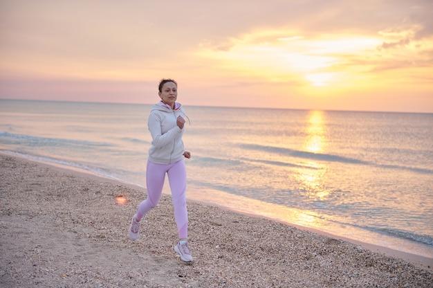 Молодая спортивная женщина в розовой спортивной одежде выполняет утреннюю пробежку вдоль побережья моря
