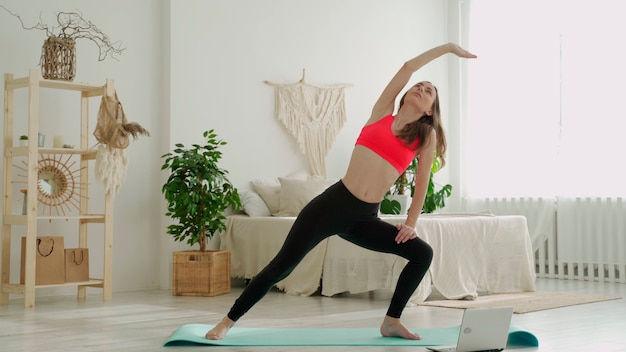 Young athletic woman in leggings and top does stretching exercises woman goes in for sports at home