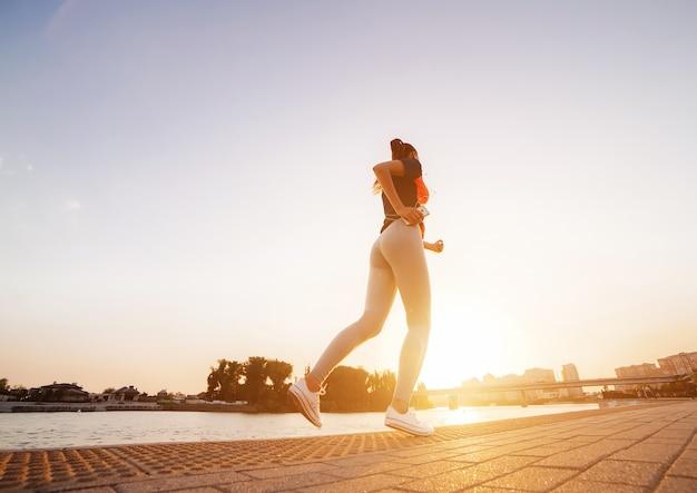 川、公園、橋を背景に、街を走っている若い運動女性。日の出