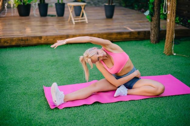 若い運動女性は健康的なライフスタイルの緑の芝生の概念にストレッチ運動を行います