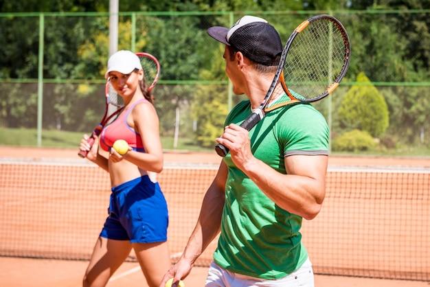 Молодая спортивная женщина играет в теннис со своим тренером