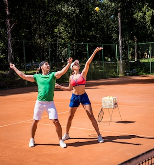 彼女のコーチとテニスをしている若い運動選手