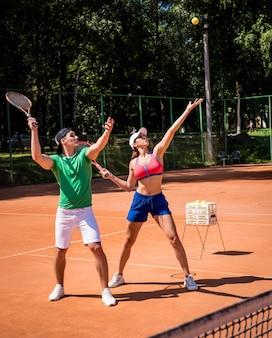 彼女のコーチとテニスをしている若い運動女性