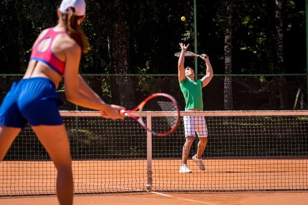 Молодая спортивная женщина играет в теннис со своим тренером.