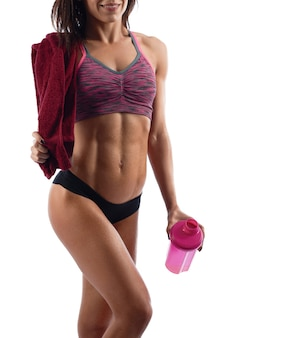 Young athletic woman posing with a towel and sports bottle after