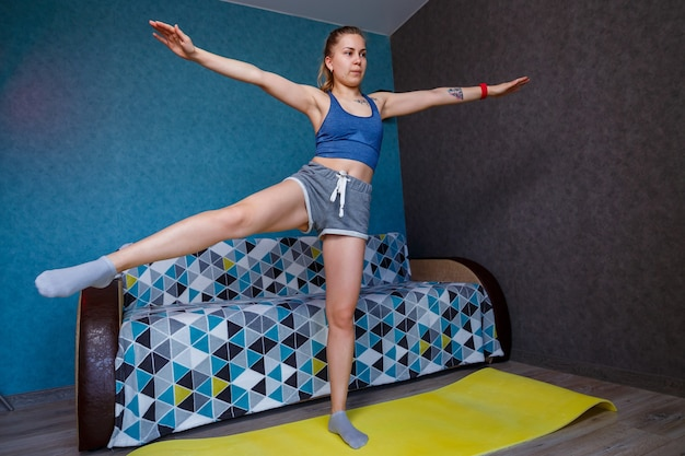 Young athletic woman practicing yoga, body stretching, exercise, legs swing to the side, training, wearing sportswear, blue t-shirt, shorts, near the sofa at home