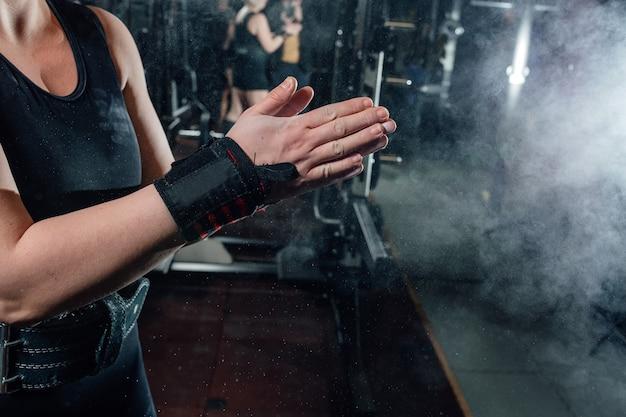 스포츠 장비와 하드 훈련을 위해 손을 준비하는 젊은 운동 여자.