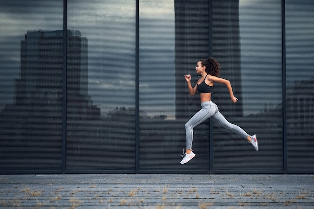 Young athletic woman running in the city shot of girl jumps on the glass building background