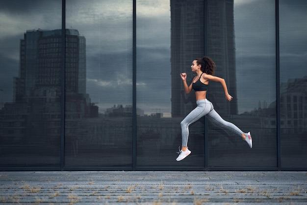 Молодая спортивная женщина работает в городе выстрел из девушки прыгает на фоне стеклянного здания
