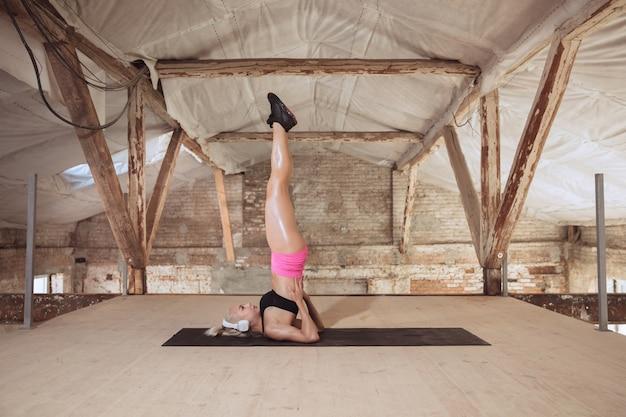 Una giovane donna atletica in camicia e cuffie bianche che risolve ascoltando la musica in un cantiere abbandonato. equilibrio. concetto di stile di vita sano, sport, attività, perdita di peso.