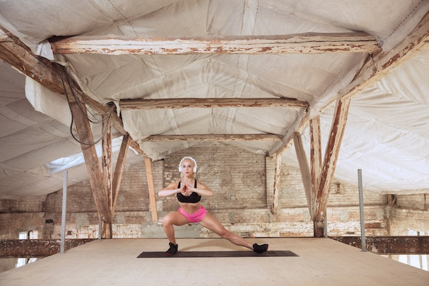 Una giovane donna atletica in camicia e cuffie bianche che risolve ascoltando la musica in un cantiere abbandonato. fare squat. concetto di stile di vita sano, sport, attività, perdita di peso.