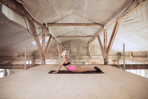 Una giovane donna atletica in camicia e cuffie bianche che risolve ascoltando la musica in un cantiere abbandonato. allungamento. concetto di stile di vita sano, sport, attività, perdita di peso.