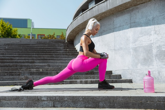 A young athletic woman in shirt and white headphones working out listening to the music at the street outdoors. doing lunges and stretching. concept of healthy lifestyle, sport, activity, weight loss.