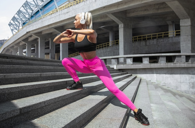 A young athletic woman in shirt and white headphones working out listening to the music at the street outdoors. doing lunges up stairs. concept of healthy lifestyle, sport, activity, weight loss.