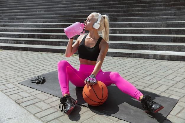 Una giovane donna atletica in camicia e cuffie bianche che risolvono ascoltando la musica all'aperto della via. riposo dopo gli esercizi. concetto di stile di vita sano, sport, attività, perdita di peso.